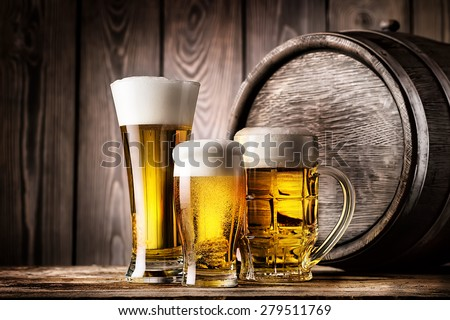 Two glasses and mug of light beer on a background of the old wooden barrels - stock photo