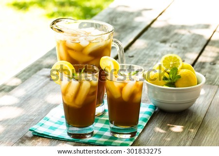 Two glasses and pitcher of iced tea with lemons on picnic table