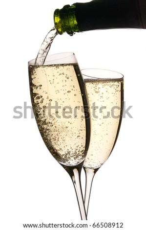 Two glasses clink in toast as sparkling wine is poured. Bubbles in the golden liquid. Isolated on white. Copy space. - stock photo
