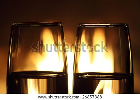 two glasses closeup in front of fireplace - stock photo