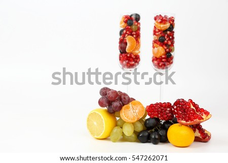 two glasses filled with fruit on a light background