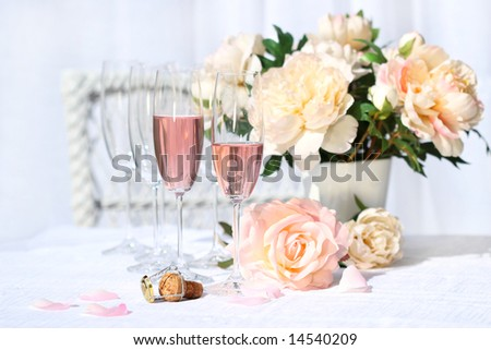 Two glasses filled with pink Champagne with flowers - stock photo
