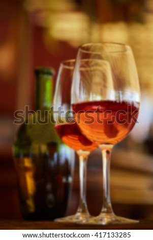 two glasses filled with red wine and bottle in background - stock photo