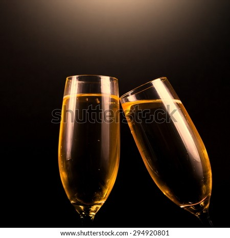 two glasses flutes golden champagne black background holiday Christmas new Year Valentine Day event luxury life drink night isolated - stock photo