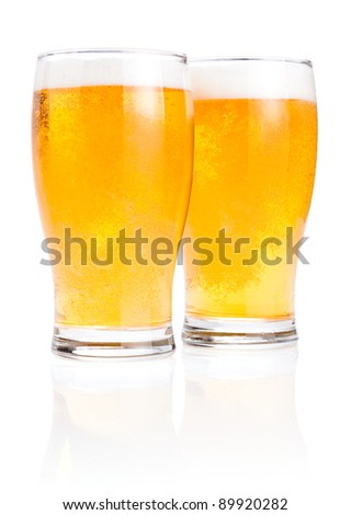 Two glasses fresh lager beer with foam Isolated on white background - stock photo