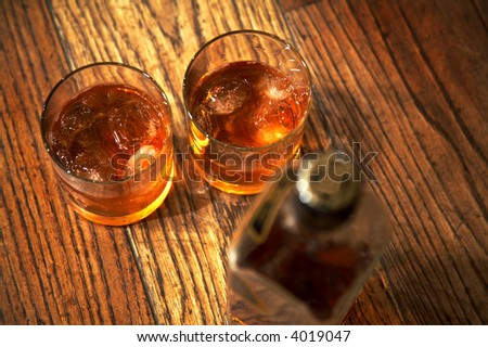 Two glasses from whisky and a bottle on a wooden table - stock photo