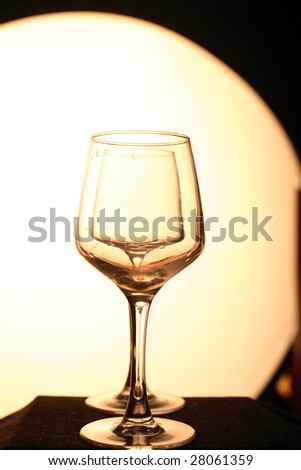 Two glasses in a row. Yellow background, dark floor. Artistic picture - stock photo