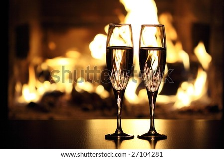 two glasses in front of fireplace - stock photo
