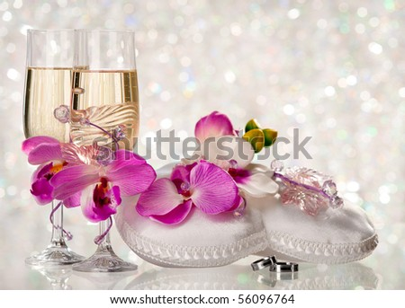 Two glasses of a champagne and pillow with wedding rings - stock photo
