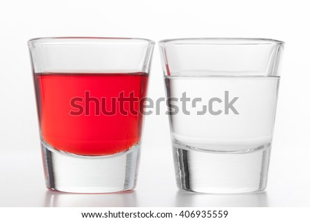 Two glasses of alcohol. One red flavoured, the other clean vodka. White background. - stock photo