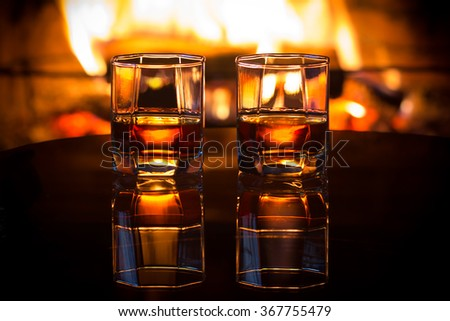 Two glasses of alcoholic drink wine and antique books in front of warm fireplace. Magical relaxed cozy atmosphere near  fire. Background horizontal