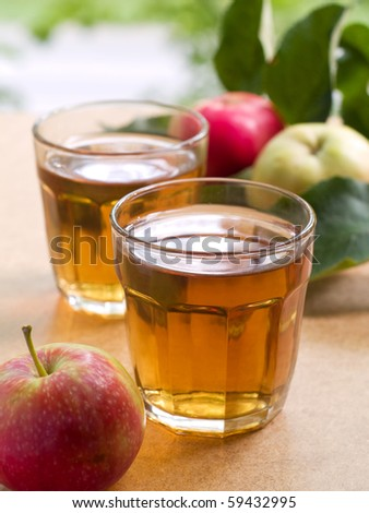 Two glasses of apple juice with apples in the background. - stock photo
