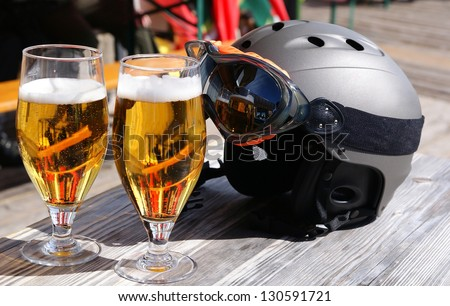 Two glasses of beer and a ski helmet on the table - stock photo