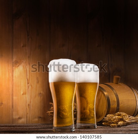 two glasses of beer, barrel and rye on wooden table. wooden background - stock photo
