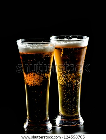 Two Glasses of Beer isolated on black background - stock photo