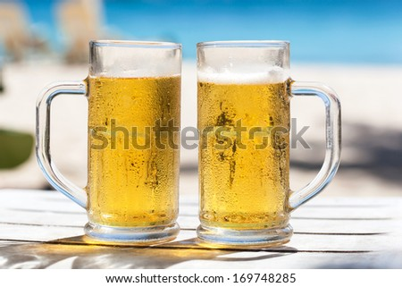 Two glasses of beer on a beach  - stock photo