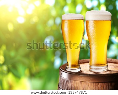 Two glasses of beer on a wooden barrel. Background - blurred sunny forest. - stock photo