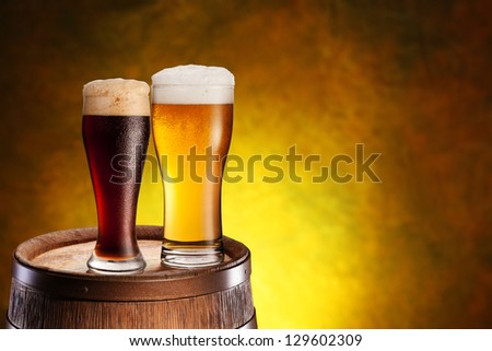 Two glasses of beer on a wooden barrel. Dark yellow background with a gradient.