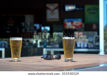 Two glasses of beer on a wooden table. Out of focus bar in background. Pair of sunglasses also on table.