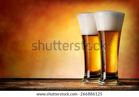 Two glasses of beer on a yellow background - stock photo