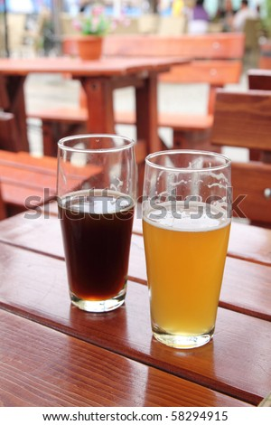 Two glasses of beer on wooden desk - stock photo