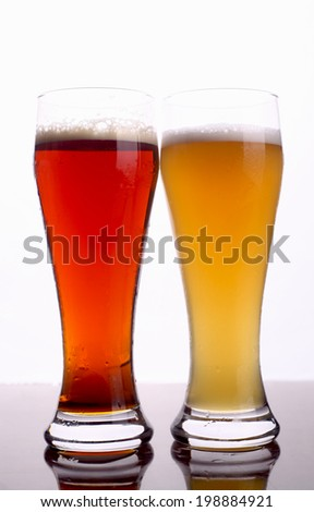 Two glasses of beer over a bright background