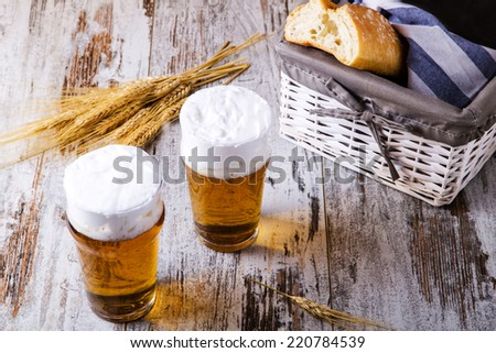 two glasses of beer with bread on rustic wooden table - stock photo