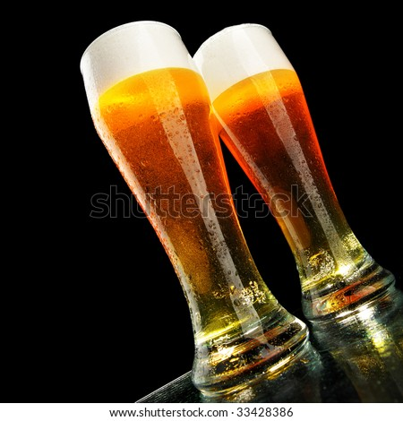 Two glasses of beer with froth over black background - stock photo