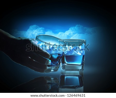 Two glasses of blue liquid with mountain illustration in - stock photo