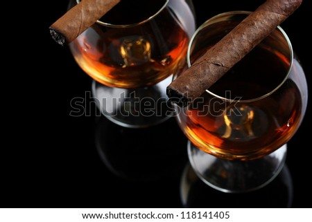 two glasses of brandy and cigars on black background - stock photo