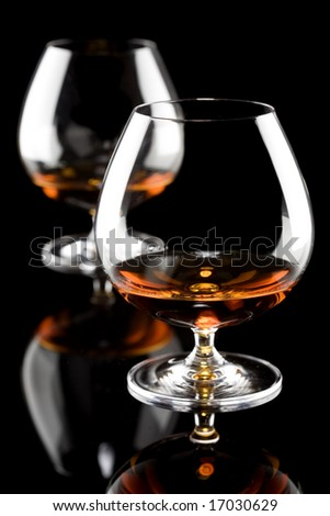 Two glasses of brandy isolated on a black background