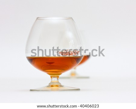Two glasses of brandy - one behind another. - stock photo