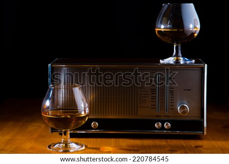 two glasses of brandy with a vintage radio, black Background - stock photo