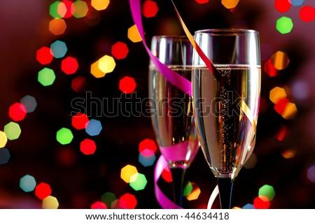 Two Glasses of Champagne against Blurred Christmas Lights. Shallow Depth of Field. - stock photo