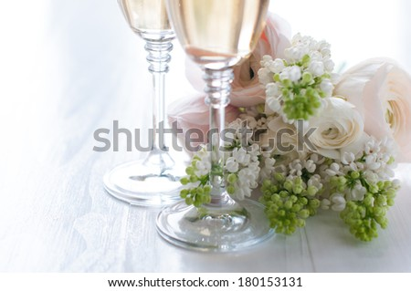 Two glasses of champagne and a beautiful tender festive wedding bouquet of flowers, buttercups and white lilac on a white painted wooden board. - stock photo