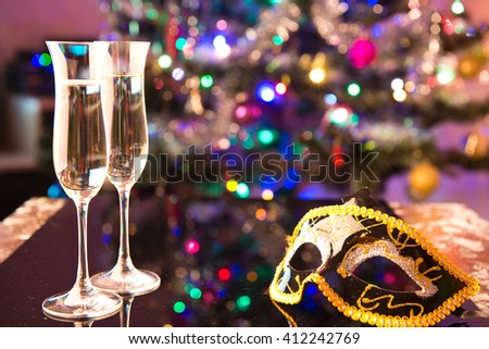 Two glasses of champagne and a black carnival mask - stock photo