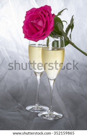 Two Glasses of Champagne and a Single Pink Rose - stock photo