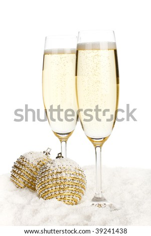 Two glasses of champagne and Christmas baubles on snow over white background - stock photo