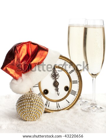 Two glasses of champagne and clocks in a Christmas cap on snow - stock photo