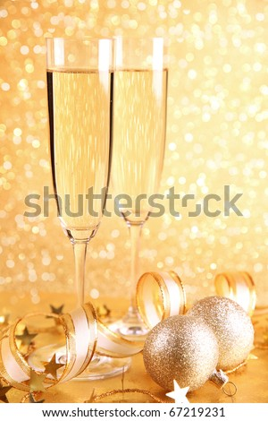 Two glasses of champagne and golden decoration - stock photo