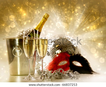 Two glasses of champagne and ice bucket against festive gold background - stock photo