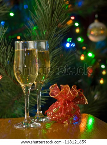 Two glasses of champagne and red gift in front of christmas tree