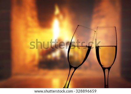 Two glasses of champagne in front of fireplace - stock photo