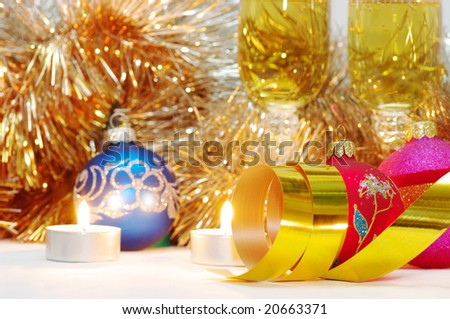 Two glasses of champagne lightening with candle in new year stuff with christmas balls