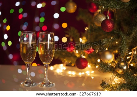 Two glasses of champagne near beautiful christmas tree  - stock photo