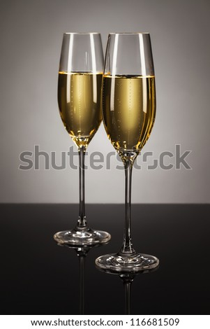 two glasses of champagne on a mirror with a spot light background - stock photo