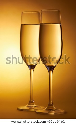 Two glasses of champagne on abstract yellow background