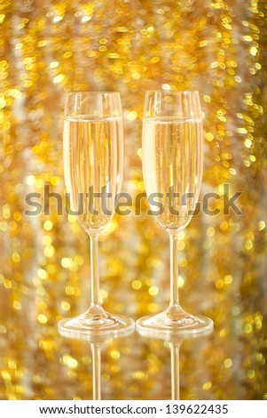 Two glasses of champagne, on an indistinct gold background