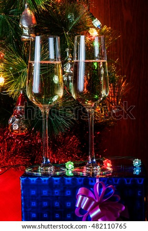 Two glasses of champagne on background christmas tree and gift. Selective focus on glasses