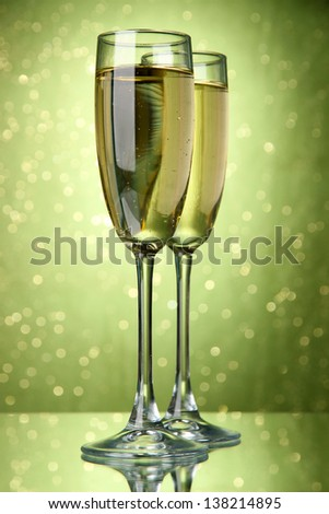 Two glasses of champagne on bright background with lights - stock photo